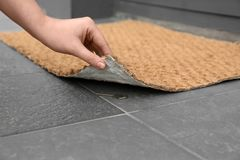 Woman lifting door mat to reveal key hidden underneath, closeup. Space for text royalty free stock photography