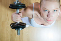 Woman lifting dumbbell in gym Stock Image