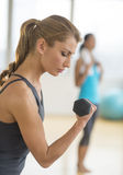 Woman Lifting Dumbbell At Health Club Stock Images
