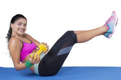 Woman lifting dumbbell and her leg on mat Royalty Free Stock Photography