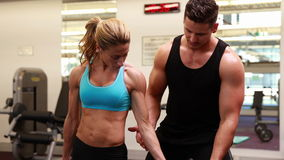 Woman lifting dumbbell with her trainer at crossfit session stock footage