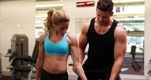 Woman lifting dumbbell with her trainer at crossfit session. At the gym stock video footage