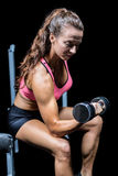 Woman lifting dumbbell while sitting on press bench Stock Images