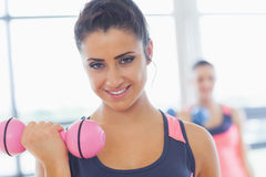 Woman lifting dumbbell weight with friend in background at gym Stock Images