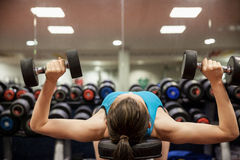 Woman lifting dumbbell weights while lying down Stock Photos