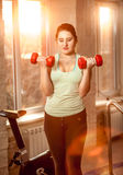 Woman lifting dumbbells at fitness club at sunset Royalty Free Stock Images