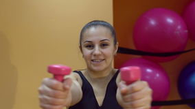 Woman lifting dumbbells in the gym and looking at the camera, slow motion. stock footage