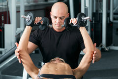 Woman lifting dumbbells with her personal trainer in the gym Stock Photos
