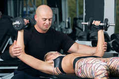 Woman lifting dumbbells with her personal trainer in the gym Royalty Free Stock Photo