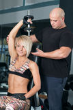 Woman lifting dumbbells with her personal trainer in the gym Stock Images
