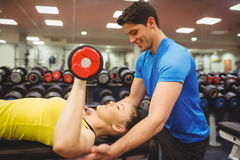 Woman lifting dumbbells with her trainer Stock Images