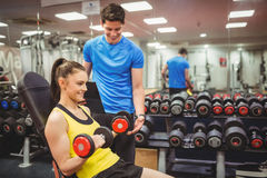 Woman lifting dumbbells with her trainer Stock Image