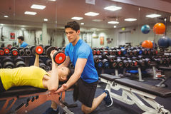 Woman lifting dumbbells with her trainer Royalty Free Stock Image