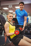 Woman lifting dumbbells with her trainer Royalty Free Stock Photos