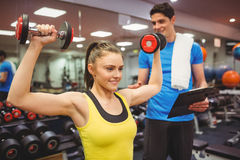 Woman lifting dumbbells with her trainer Royalty Free Stock Photo
