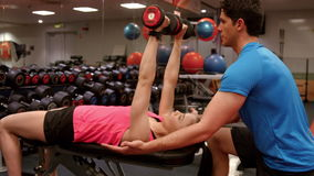 Woman lifting dumbbells with her trainer. In high quality 4k format stock video footage