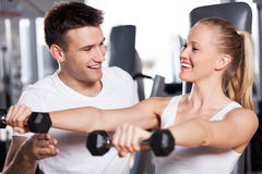 Woman lifting dumbbells while instructor assisting Stock Photography