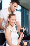 Woman lifting dumbbells while instructor assisting. Young couple in health club Royalty Free Stock Photo