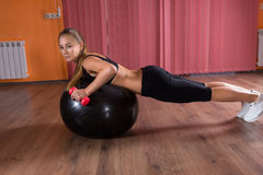 Woman Lifting Hand Weights on Exercise Ball Stock Image