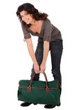 Woman lifting heavy bag Stock Photography