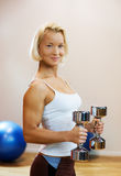 Woman lifting heavy dumbbells Stock Photography