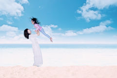 Woman lifting her daughter at beach Royalty Free Stock Image