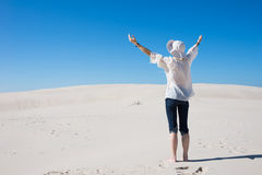 Woman lifting her hands up in the air standing on sand dune Stock Image