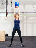 Woman lifting a kettle bell over her head. Photo of a young woman exercising with a kettle bell at a gym Royalty Free Stock Images