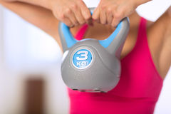Woman lifting kettlebell Stock Photography