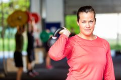 Woman Lifting Kettlebell At Gym Stock Photos