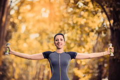 Woman lifting small weights in the park Royalty Free Stock Image