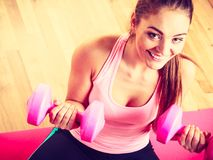 Woman lifting two dumbbells. Young girl exercising in gym. Health workout fitness concept Royalty Free Stock Image