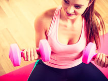 Woman lifting two dumbbells. Young girl exercising in gym. Health workout fitness concept Royalty Free Stock Images