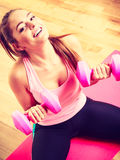 Woman lifting two dumbbells. Young girl exercising in gym. Health workout fitness concept Stock Photo