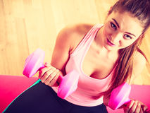Woman lifting two dumbbells. Young girl exercising in gym. Health workout fitness concept Royalty Free Stock Photos