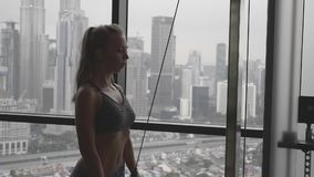 Woman Lifting Weight. Female body builder using a weights machine in the gym.Active woman workout triceps muscles pulling cable machine in fitnesss club in slow stock footage