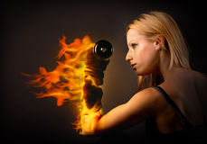 Woman lifting a weight on fire Stock Photography