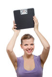 Woman lifting a weight scale over her head Royalty Free Stock Images