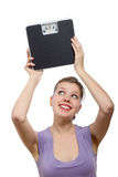 Woman lifting a weight scale over her head Stock Photos