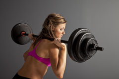 Woman Lifting Weights. Attractive young woman with barbells on shoulder Stock Photography
