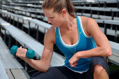 Woman Lifting Weights on Bleachers at Outdoor Track Stock Photo