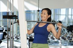 Woman Lifting Weights On A Lat Pull Machine. Happy Chinese woman in the gym lifting weights on a lat pull machine stock images