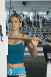 Woman Lifting Weights On A Lat Pull Machine. Woman in the gym lifting weights on a lat pull machine Royalty Free Stock Image