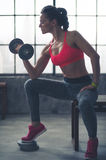 Woman lifting weights sitting on bench in loft gym. A fit, muscular woman sitting on a city loft gym bench is lifting weights, resting her elbow against her knee Royalty Free Stock Images