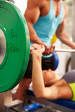 Woman lifting weights with trainer, focus on barbells Royalty Free Stock Photo