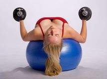 Woman lifts dumbbells on stability ball. Woman lies on stability ball while exercising arms with dumbbells Stock Image