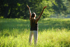 Woman lifts hands to the top in forest. Yoga Stock Photo