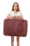 Woman lifts a heavy suitcase, isolated on white Stock Image