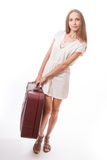 Woman lifts a heavy suitcase, isolated on white Royalty Free Stock Photography