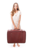 Woman lifts a heavy suitcase, isolated on white Stock Photo